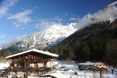 Chalet in French Alps in Chamonix with a panorama of mountains covered in snow in winter. Chalet and a hut in French Alps in Chamonix with a panorama of Royalty Free Stock Photos