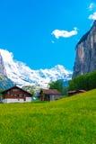 Chalet på grön berglutning schweiziska alps Lauterbrunnen Swit Fotografering för Bildbyråer