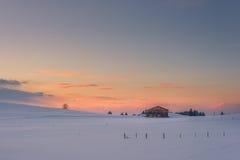 Chalet solo sul prato nevoso al tramonto di inverno Immagine Stock