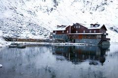Chalet sur le lac Balea entouré par des montagnes Photographie stock libre de droits