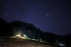 Chalet under the stars, visible Milky Way galaxy, clear sky, long exposure. Astrophotography Stock Image