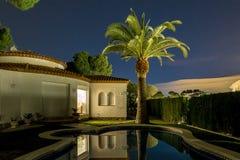 Chalet y palma agradables en la noche en España Fotos de archivo