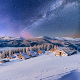 Chalets dans les montagnes la nuit sous les étoiles Photos stock