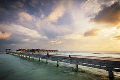 Chalets de madera del embarcadero y del agua Centro turístico isleño de Maldivas en la puesta del sol imágenes de archivo libres de regalías