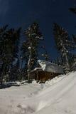 Chalets de maison de carlingue dans la forêt d'hiver avec la neige en lune légère et Image stock