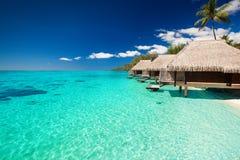 Chalets en la playa tropical con pasos de progresión en el agua