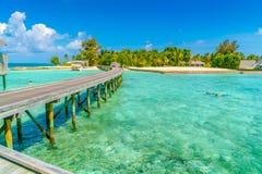 Chalets hermosos del agua con los pares que bucean en Maldi tropical Imagen de archivo