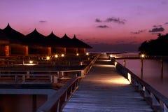 Chalets Maldivas del agua de la puesta del sol Imágenes de archivo libres de regalías