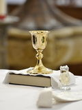 Chalice bible and holy water. Christian chalice, bible and baptismal water in a pitcher stock photos