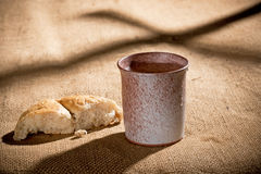Chalice And Bread. Still life with chalice and bread on the textile tablecloth royalty free stock images