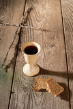 Chalice and bread on the wooden table Stock Photos