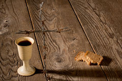 Chalice and bread on the wooden table Stock Image