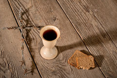 Chalice and bread on the wooden table Royalty Free Stock Photography