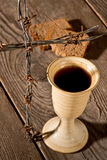 Chalice and bread on the wooden table Royalty Free Stock Images
