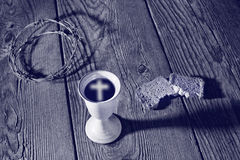 Chalice and bread on the wooden table Stock Images