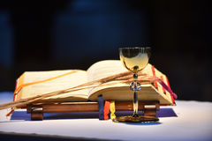 Chalice and open prayer book. Elegant golden chalice with open prayer book in the background Stock Photo