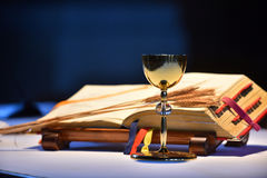 Chalice and open prayer book. Elegant golden chalice with open prayer book in the background royalty free stock photography