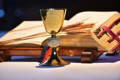 Chalice and open prayer book. Elegant golden chalice with open prayer book in the background Royalty Free Stock Photos