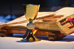 Chalice and open prayer book. Elegant golden chalice with open prayer book in the background Stock Photography