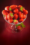A chalice of strawberries. On dark red background royalty free stock photo