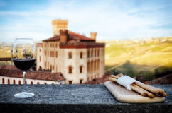 Chalice of wine with breadsticks and the castle of Barolo Italy Royalty Free Stock Photo