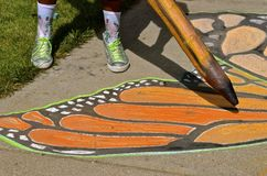 Chalk art of a butterfly wing. A huge pencil is being used to color in black on a Monarch Butterfly wing in a chalk artist drawing stock photography