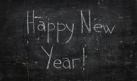 Chalk on black board: Happy new year Stock Image