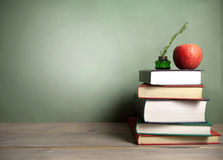Chalk  board background with books. Stack of books with apple and quill next to a chalkboard background Stock Photography