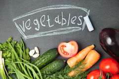 chalk board background with  onion, garlic , parsley , cucumber , eggplant , tomato and dill. Top view Stock Photos