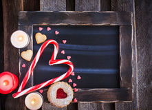 Chalk board and heart shaped candies and cookies Stock Photos