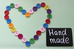 Chalk Board with the inscription `handmade` surrounded by a heart of colored buttons on a light background stock image