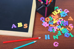 Chalk board, letters and pencils Royalty Free Stock Photography