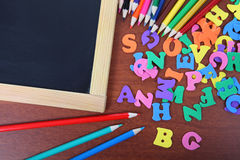 Chalk board, letters and pencils Stock Image