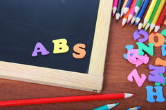 Chalk board, letters and pencils Stock Photo