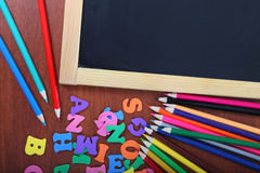 Chalk board, letters and pencils Royalty Free Stock Photos