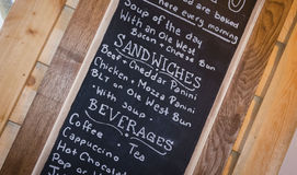 Chalk board with a menu of food and beverages. Horizontal image of a slanted image of a menu written on a black chalkboard Royalty Free Stock Photography
