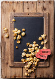Chalk board with popcorn and movie tickets. Vintage slate chalk board with popcorn and two movie tickets on wooden background Royalty Free Stock Images