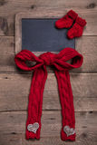 Chalk board with red knitted sock and bow on wooden background Royalty Free Stock Photos