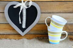 Chalk board in the shape of a heart and two cups Stock Photos