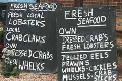 Chalk board signs advertising fish for sale stock photo