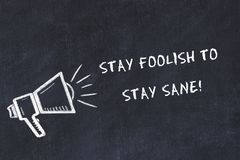 Chalk board sketch with loudspeaker and motivational phrase stay foolish to stay sane.  royalty free illustration