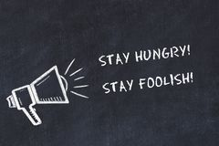 Chalk board sketch with loudspeaker and motivational phrase stay hungry stay foolish stock illustration