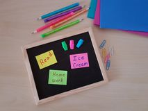 Chalk Board With Sticky Notes, Erasers and Pencils stock photo