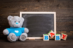 Chalk board and  teddy bear on a wooden background Royalty Free Stock Image