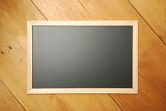 Chalk board top view with wooden background stock photography