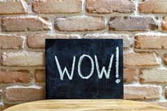 Chalk board with the word WOW! drown by hand and chalks on wooden table on brick wall background. For presentation stock photos