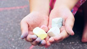 Chalk in child`s hands close-up. The child drawing a chalk on asphalt. Child drawings paintings on asphalt concept. Chalk in child`s hands close-up. The child stock photos