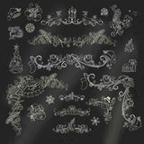 Chalk Christmas calligraphic design elements on blackboard background. Royalty Free Stock Photo