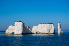 Chalk cliff face with cave at bottom. Chalk cliff face on coast with cave at bottom stock photos