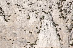 Chalk cliff face with cave at bottom. Chalk cliff face on coast with cave at bottom royalty free stock image